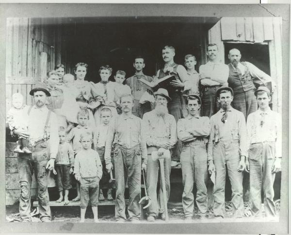 Furnace manager William H. Womer is on the right, back row, with a strap holding a wooden box over his shoulder. Notice the man holding the open book in the center of the photo. The man standing to the left of him is holding a doll.