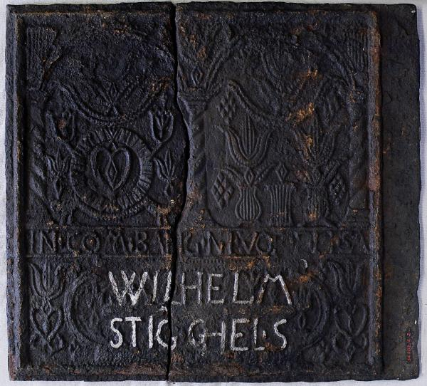 "Photograph of a Cast-iron stove plate features the words ""Wilhelm/Steigels""."