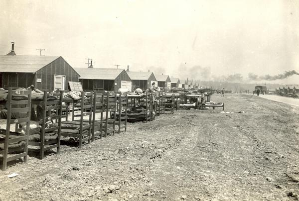 Photograph of the outdoor bunks in rows along the barracks buildings.