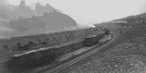 One can see the long lines of Bee-hive coke ovens located in the valley at Morewood, with the wooden railroad coke cars being loaded with coke.