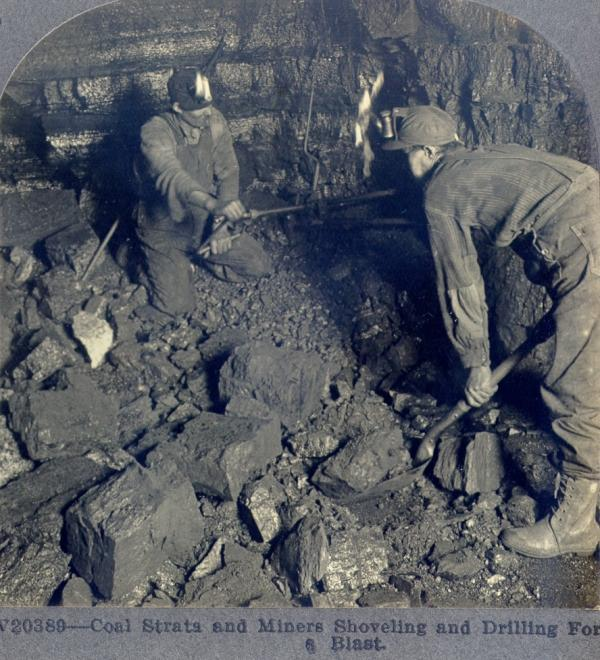 Black and white photograph showing two miners shoveling and drilling for a blast.