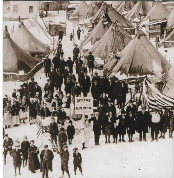 A large tent colony of evicted strikers and their families fill this photograph.