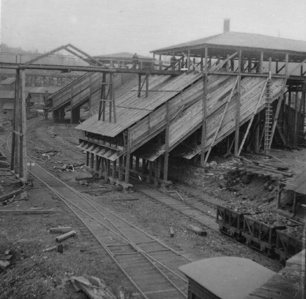 Black and white image of a coal chute, coal filled railroad cars, and several rows of track.