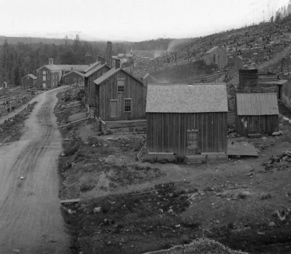 Black and white photograph of a dirt road lined with small, stark houses. In the background sits a large building.