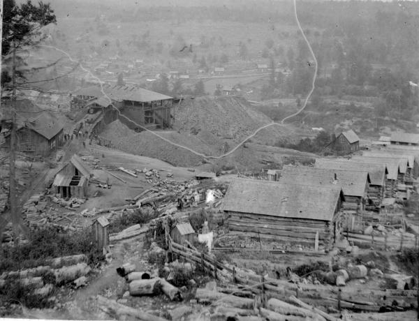 In the background of this photograph is the east mines. One can see the chute, workers, and stacks of coal refuse. In the foreground is a row of patch houses and yards.