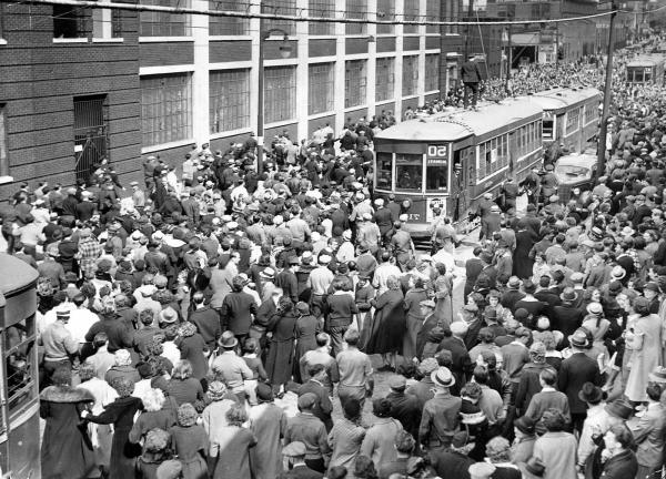 A large crowd forms in a public street surrounding cable cars and stopping  traffic.