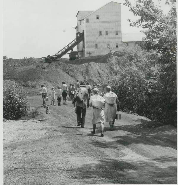 Black and white image of migrant workers carrying cans of berries on their backs