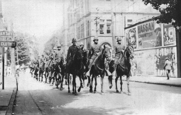 A large group of mounted police ride down the middle of the road in threes.