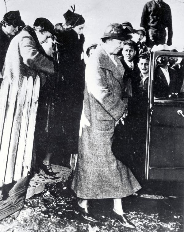 Eleanor Roosevelt stands about to enter an automobile. Doris Duke, tobacco heiress wearing a black coat, and others stand behind her.