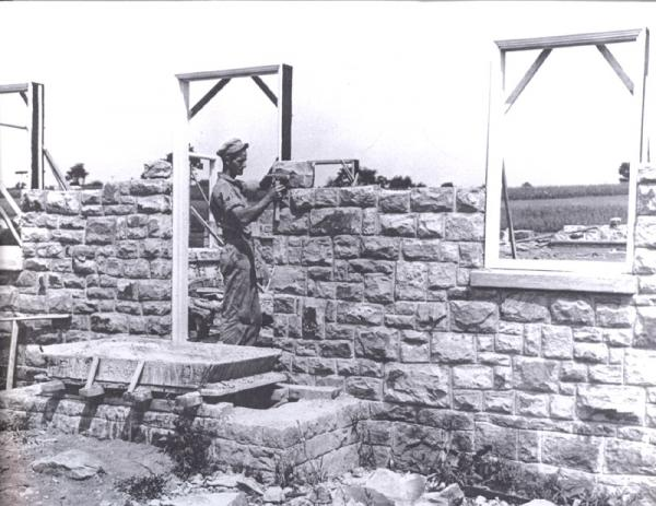 A man lays brick to construct the wall of a house.