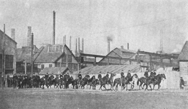 Cossacks on horseback leaving a steel mill.