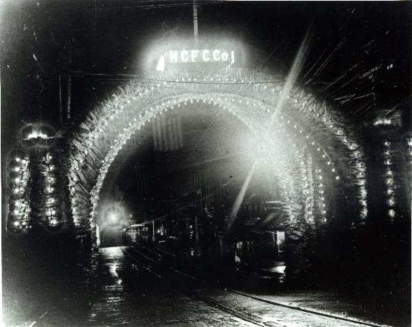 A huge coke arch stretches across the width of a street. On the top of the arch is a sign that reads: HCFC Co. The entire arch is lit up and looks like a magical entrance to a city.