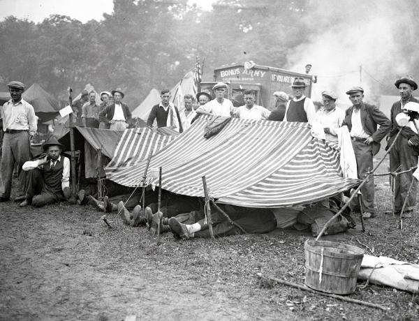 Photo Shows - A group of veterans from Spokane, Washington, resting under a canvas, as rain today, turned the camp into a muddy field.