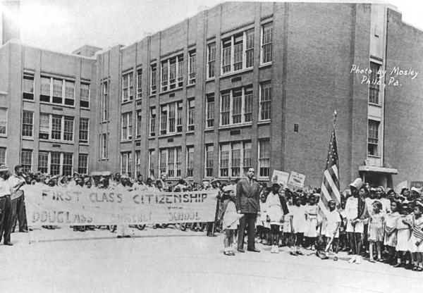 Dr. Arthur Huff Fauset in front of Singley Douglas School with a First Class Citizenship banner and students during a May Day Celebration.