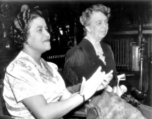 Two women seated and clapping their hands in applause.