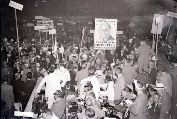 A view of a crowd at the Democratic National Presidential Convention. An FDR picture on a poster is in the middle of the photo.
