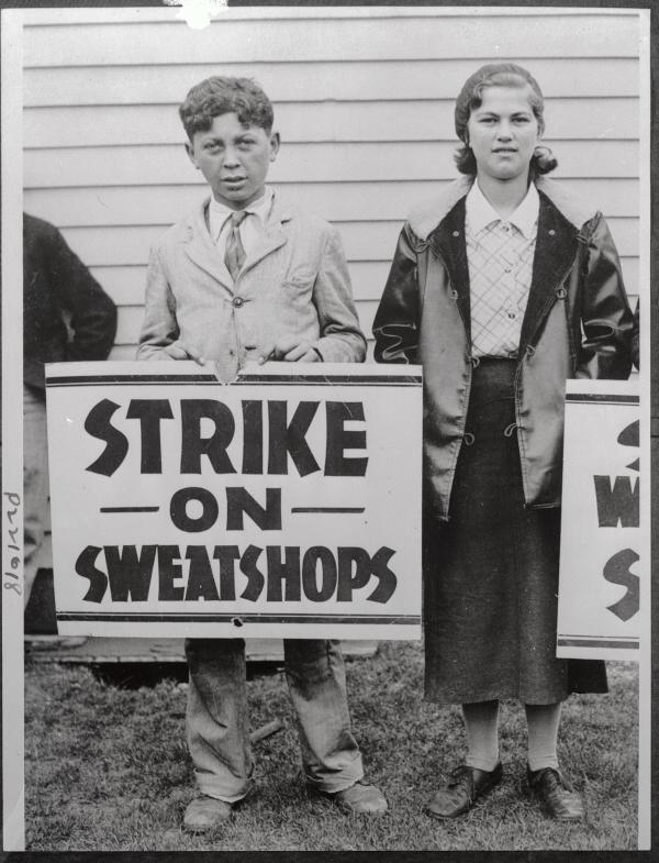 Photograph of a boy and a girl holding strike against sweat shop signs.