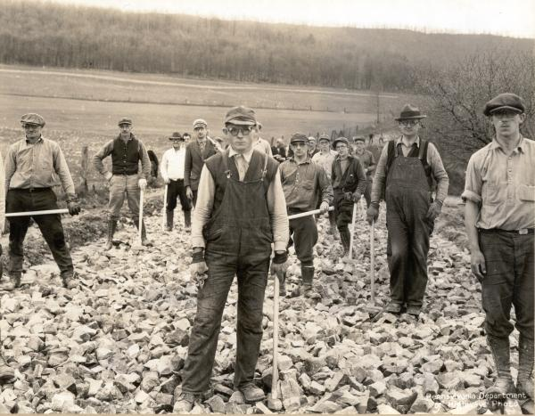 Photograph of road-bed construction and all workers facing the camera,  wearing goggles. Most of the workers hold sledge hammers in one hand.