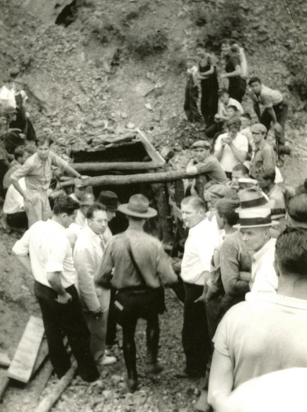 Policeman and miners stand at the entrance of a mine.