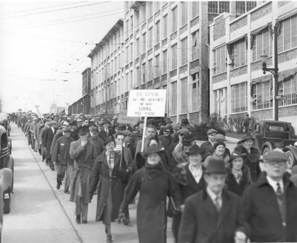 Loyalty Parade; men and women workers are marching; holding signs that read: Down With Communistic Idiotic Laws, CIO Can't Make a Monkey Out of Us, and Hershey Fills Our Breadbaskets, not the CIO