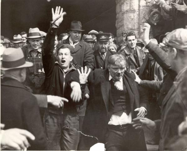 Hershey Chocolate; sit-down strike; workers leaving factory, April 7, 1937.  John Loy, a worker, has a bloody nose. There is also a man with his hand raised holding a weapon.