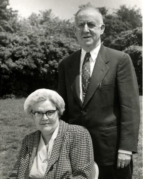 A man standing next to a woman sitting, both posing for this black and white photograph.