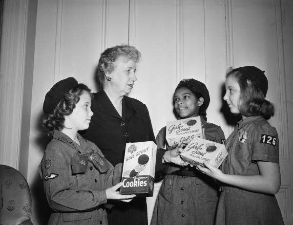 Mrs. Harry S. Truman, wife of the President, opens the 1951 Girl Scout cookie sale by accepting the first box of cookies at Blair House from three representatives of the National Capital Federation of Girl Scouts. L to r are Tommie Andersn, 12, Mrs. Truman, Gloria Williams and Joy Rice.