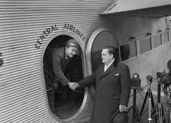 The photo shows Helen Richey, and Assistant Postmaster General W.W. Howes as he wished her luck when the young lady took the controls of the Central Airlines plane.