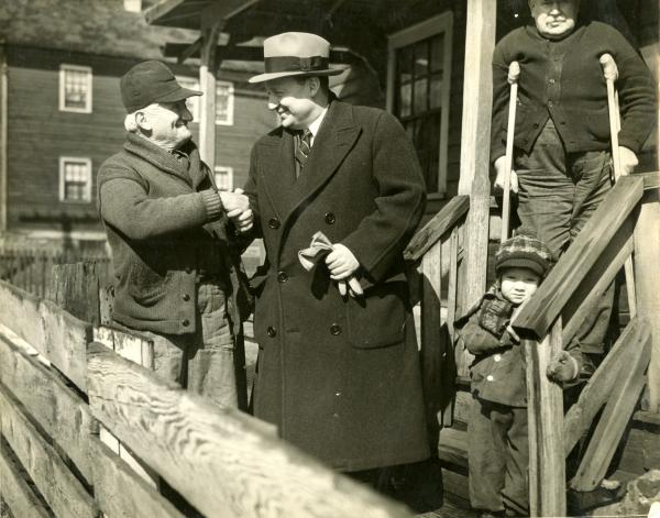 Governor Earle shakes the hand of one miner as another miner stands on crutches on the porch above them. A small child stands at the bottom of the stairs.