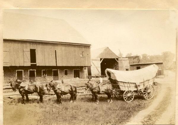 A Conestoga Wagon and team of six horses stand in front of a barn and open wagon shed.