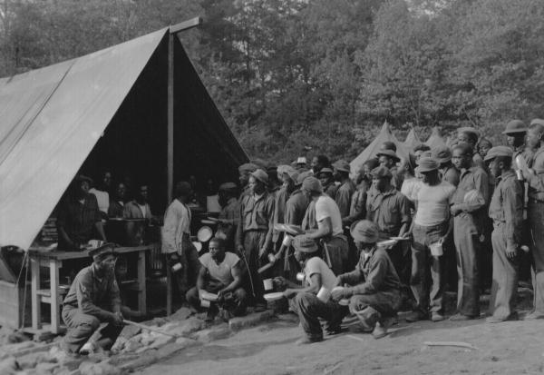 Photograph of men gathering at the mess tent for dinner.