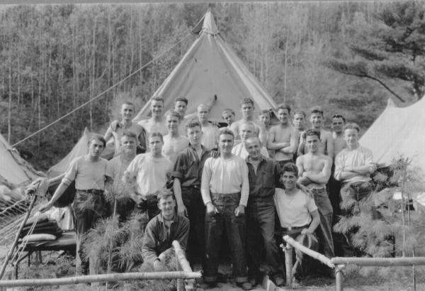 Group photograph of men posed outside of a tent.
