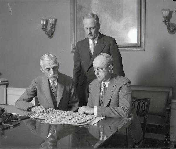 Secretary of the Treasury Andrew Mellon pictured with Assistant Secretary Henry Herrick Bond (seated) are shown the new bills by Director Hall of the Bureau of Engraving and Printing.