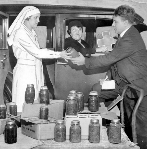 Red Cross worker hands a jar of food to a man. A woman holding a cross sign sits in a car.