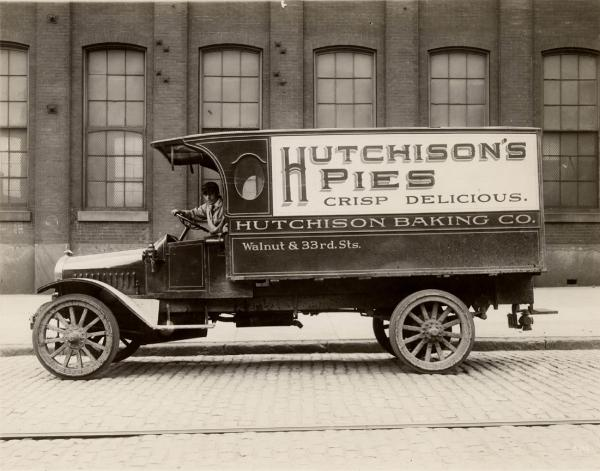 Black and white image of a Hutchinson Baking Company Truck. On the side of the truck is a sign which reads: Hutchinson Pies Crisp and Delicious.