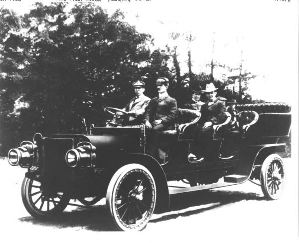 Image of a long automobile with four rows of seats. Men are seated in the rows.