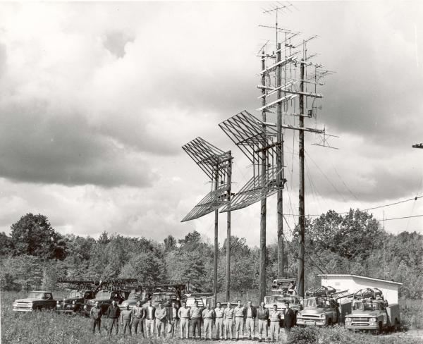 A black and white photograph of a group of antennas that made up the Barco cable system. A group of people pose in front of the antennas and several parked trucks.
