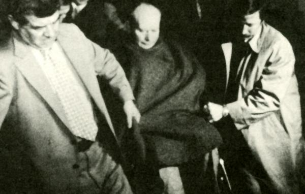 Tony Boyle, covered with a blanket and sitting in a wheel chair, is carried into the courtroom by two men.