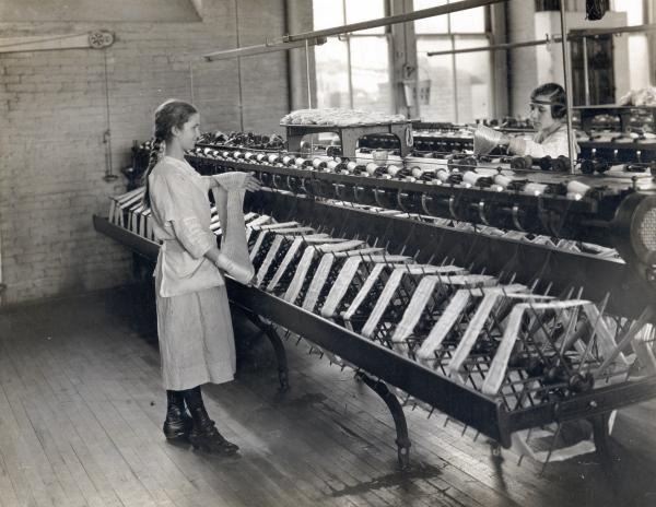 Two young women standing in front of machines in a silk mill factory wind the silk around their hands.
