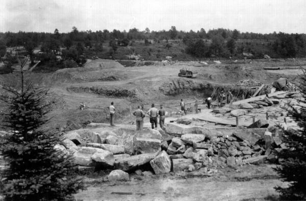 Black and white image of dam in the midst of construction. Bolders and pine in foreground. Several men observing and working.