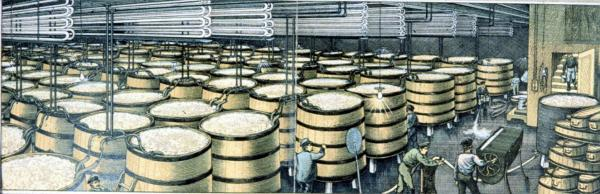 Men work in a room filled with full barrels.