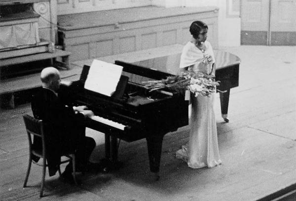 A man wearing a tuxedo sits at the piano and a woman in formal wear stands beside the piano.
