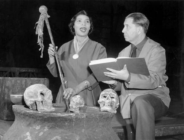 A man holding a book and a woman singing are on a stage with props.