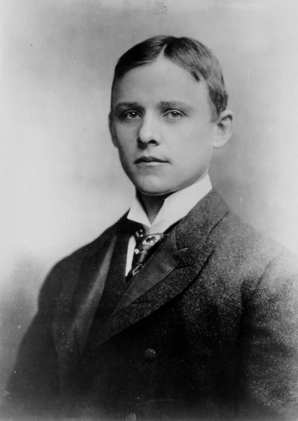 Black and white portrait of a young man in a suit.