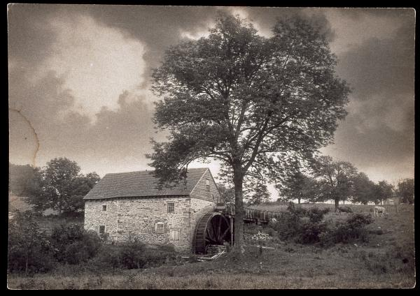 Black and white image of stone mill under tree on the right, with a cloudy sky.