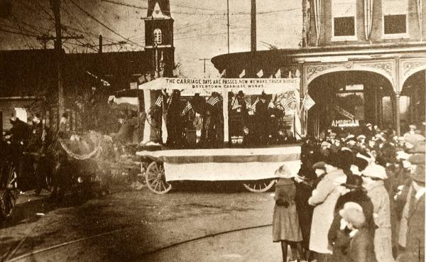 Men holding American Flags ride in a covered float with a sign that reads:Carriage Days are Past Now We Make Truck Bodies, Boyertown Carriage Works. A crowd of onlookers stand along the right side of the photograph.