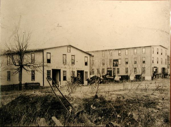 Sepia photograph of two large buildings with many windows.