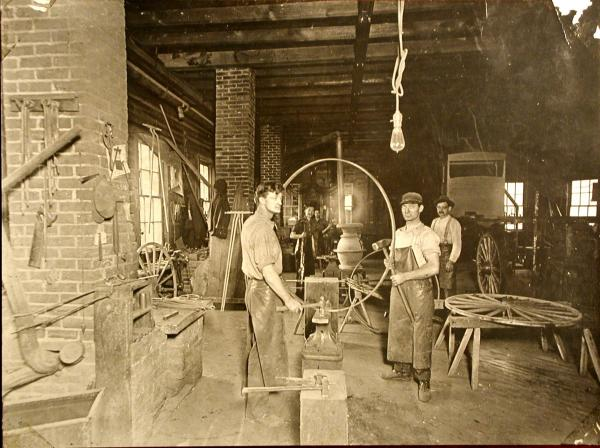Interior of the shop, workers with tools, and carriages.