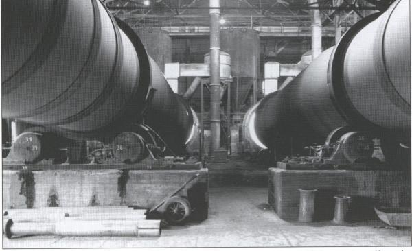 Image of rotary cement kilns inside of a factory.