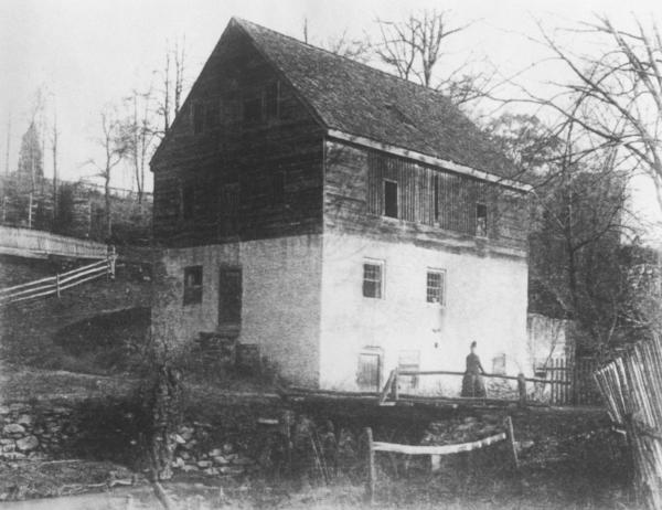 Black and white photograph of a mill. A woman stands near the entrance.